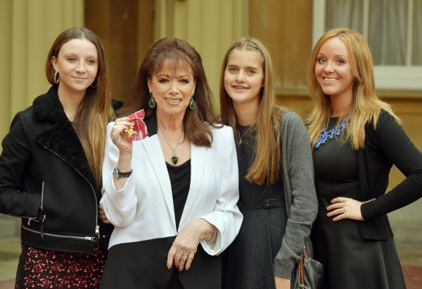 Jackie Collins with her granddaughters (L-R: Dylan Thain, Chloe Green, and India Thain) as she holds her OBE in 2013