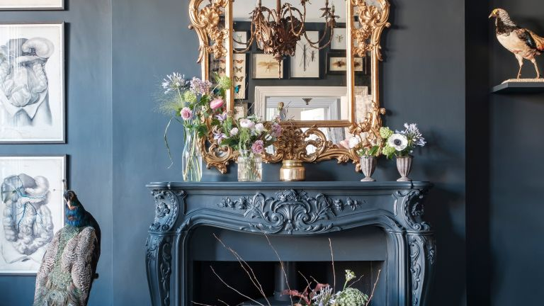 Black living room with gold mirror above the mantel