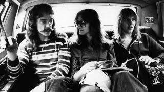 Neil Peart, Geddy Lee, Alex Lifeson - posed, group shot - sitting in back of car on All The World's A Stage tour, 1977