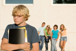 A teen boy stands apart from other students.