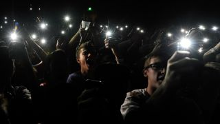 Fans using their smartphones to record a concert