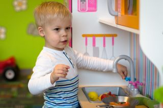 Little boy is playing in the preparation of a meal on a plastic toy kitchen.