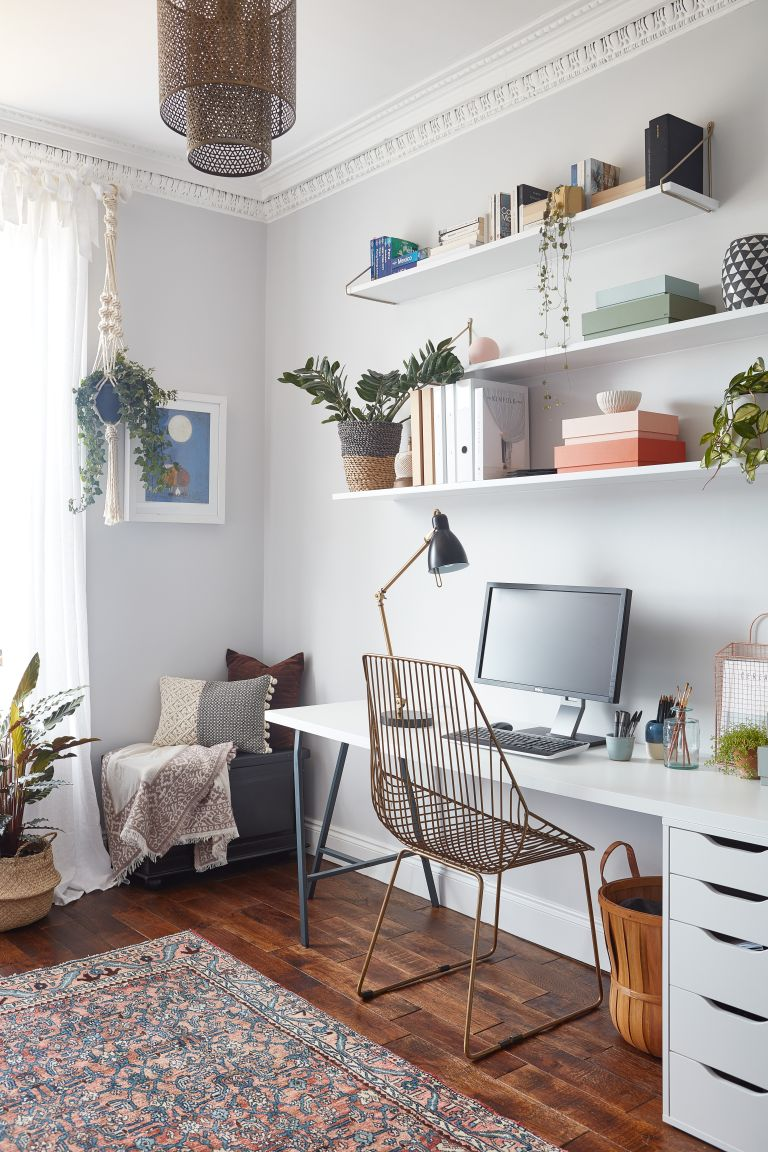 Home office with open shelving and simple white desk with drawers
