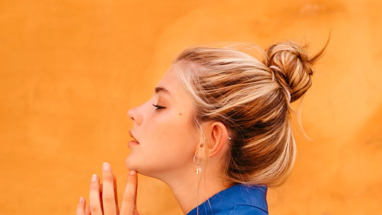 Woman with hair bun against yellow wall - stock photo
