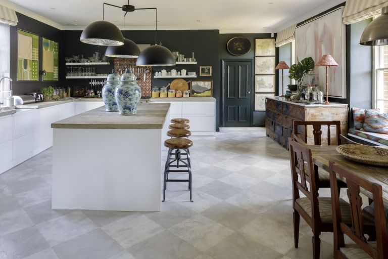 Large, modern kitchen with bright kitchen island, base cabinets, work surfaces and tiled flooring and contrasting grey/black painted walls