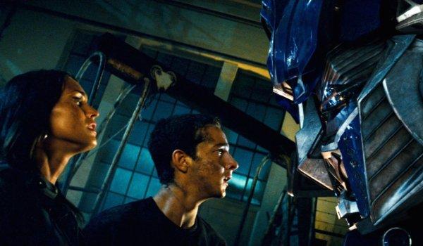 Transformers Mikaela and Sam meeting Optimus Prime near a warehouse