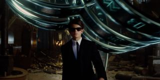 Artemis Fowl wears a suit and sunglasses as he walks away from rubble in a scene from the film.