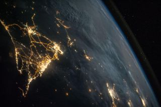 The International Space Station flies over a city at night. Human activity may be pushing the climate beyond a 'tipping point,' a new report suggests.
