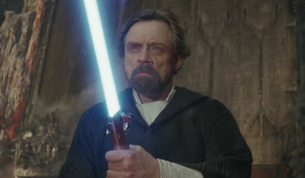 Mark Hamill as Luke Skywalker with lightsaber in Star Wars: The Last Jedi