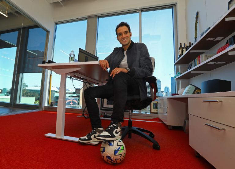 Will Ahmed sits in an office with his foot on a soccer ball