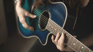 A guitarist plays an ocean blue acoustic guitar