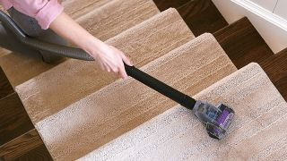 Someone cleaning pet hair from stairs