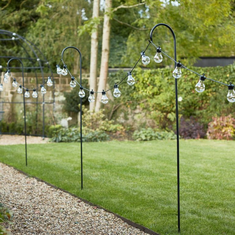 An example of outdoor string lighting ideas showing lights along a garden path