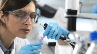 A woman works in a lab as a pharmaceutical researcher or geneticist, which is part of the STEM fields.