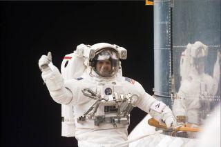 NASA astronaut Steve Smith gives a thumbs-up signal during a spacewalk.