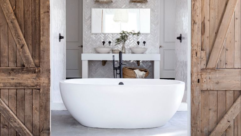Farmhouse bathroom with white tub, woven ceiling lamps and barn door entrance
