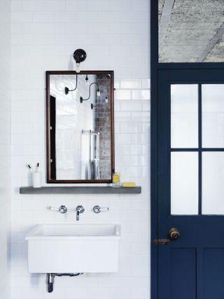 Ванная комната с большим зеркалом и темно-синей дверью