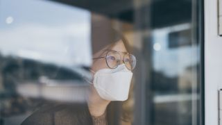 Do HEPA filters remove viruses? Image of person with mask looking out of window