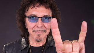 A portrait of Tony Iommi doing the horns