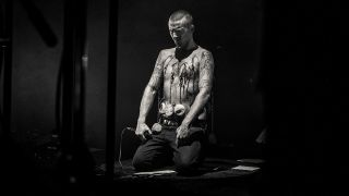a shot of amenra on stage with hooks and rocks attached to his chest