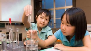 Two kids work with clear liquid in a beaker