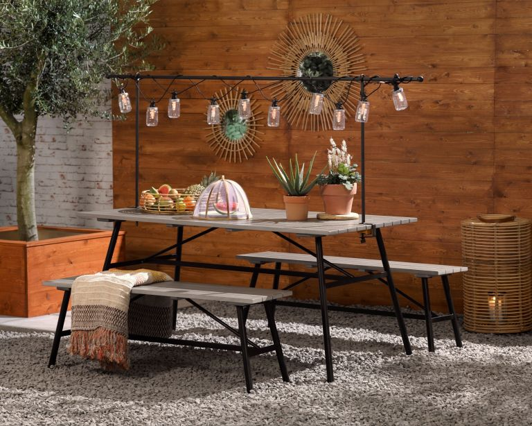 An example of how much does outdoor lighting cost showing a patio with a dining table, benches and outdoor string lights