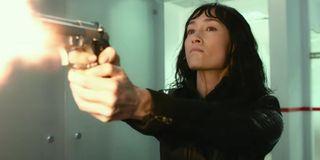 Maggie Q angrily firing a gun in The Protégé.