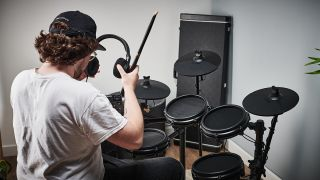 Drummer puts on a pair of headphones before playing an electronic kit