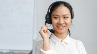 Woman using VoIP headset with high VoIP QoS smiling