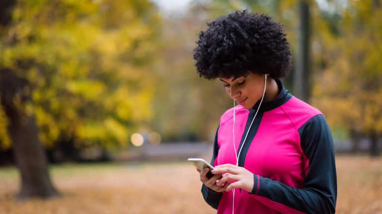 Women wears headphones and is on her phone before she begins a run outside