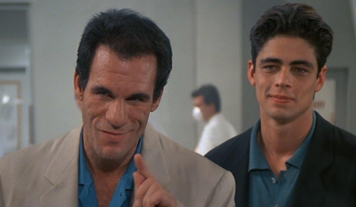 License To Kill Robert Davi and Benicio del Toro smirk together on the factory floor