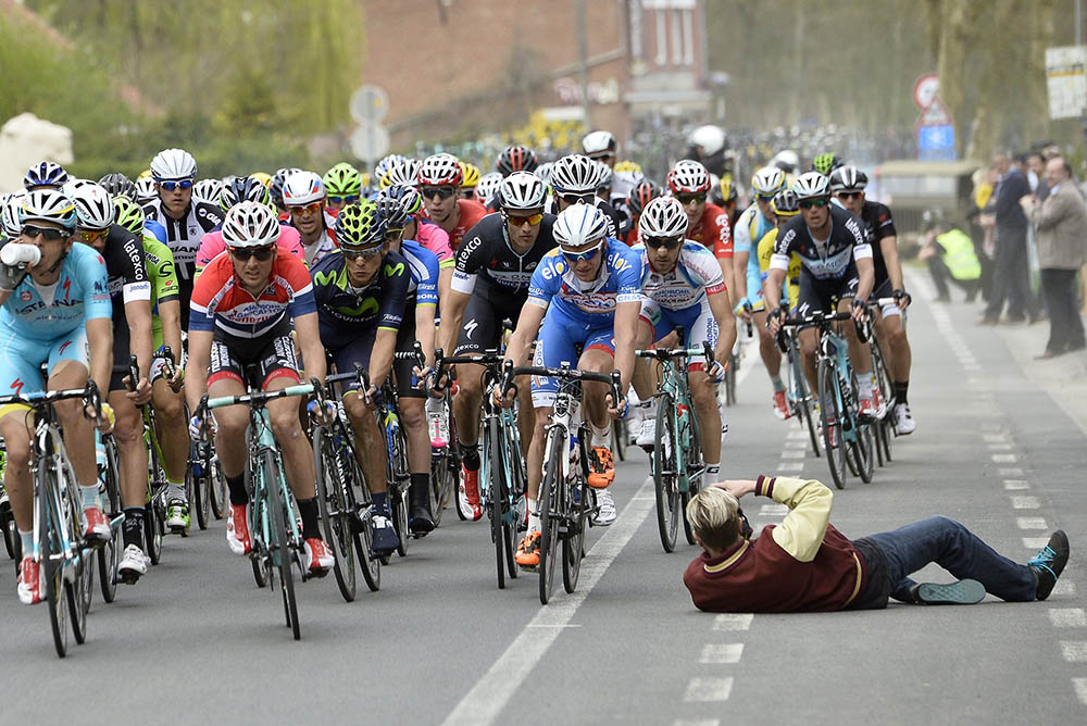 Thumbnail Credit (cyclingweekly.co.uk): A fan takes a photo in front of the peloton in the 2014 Ghent-Wevelgem