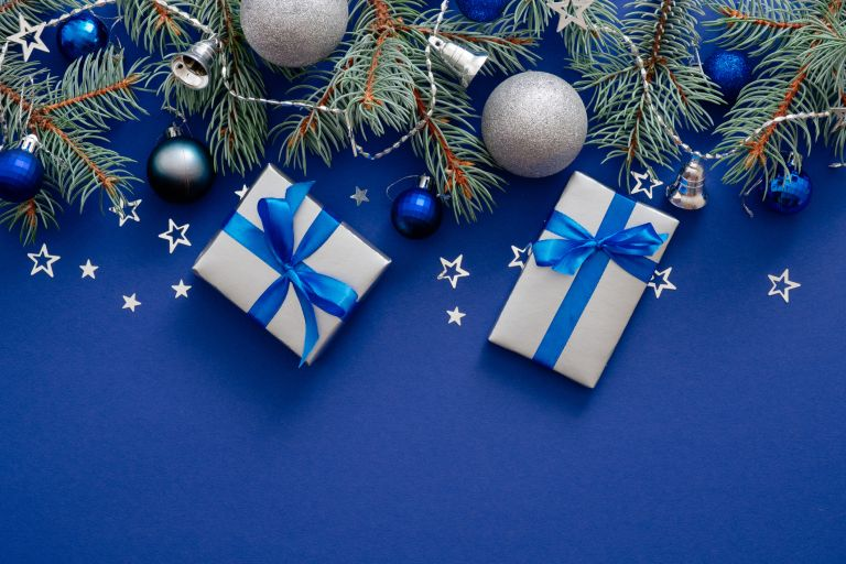 Silver presents on a blue background with festive foliage