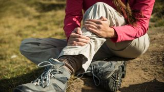 woman clutching her leg after suffering hiking injuries