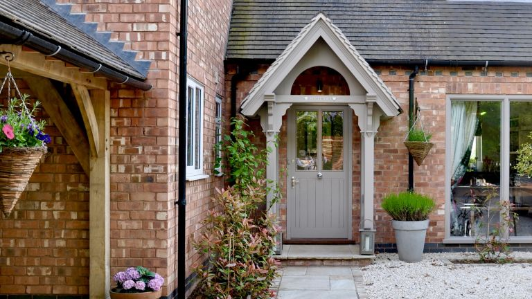 An example of front porch design showing a front porch area with a pitched roof and hanging baskets