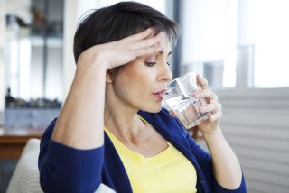 A woman with a hot flash drinking water
