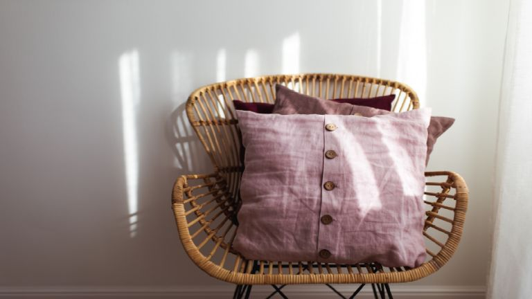 Pink envelope cushion on a whicker chair