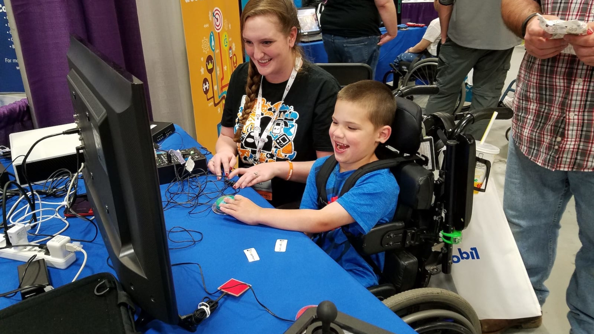 A young disabled boy playing video games with some adaptive controllers