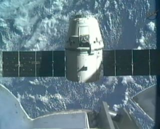 SpaceX's first Dragon space craft to the International Space Station backs away from the Canadarm2 robotic arm to begin the return trip to Earth on May 31, 2012