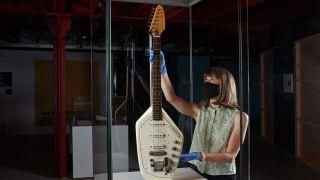 Curator installing Ian Curtis's Vox Phantom VI guitar into the museum exhibition