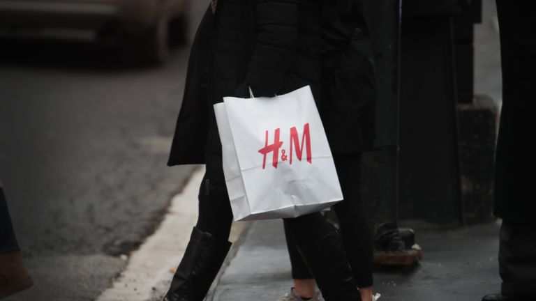 H&M Black Friday sale: shopper walks along the Magnificent Mile with a bag of merchandise from H&M