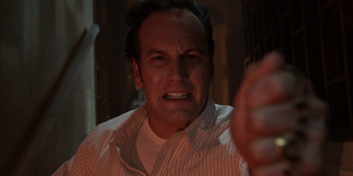Patrick Wilson as Ed Warren holding up a cross in The Conjuring: The Devil Made Me Do It