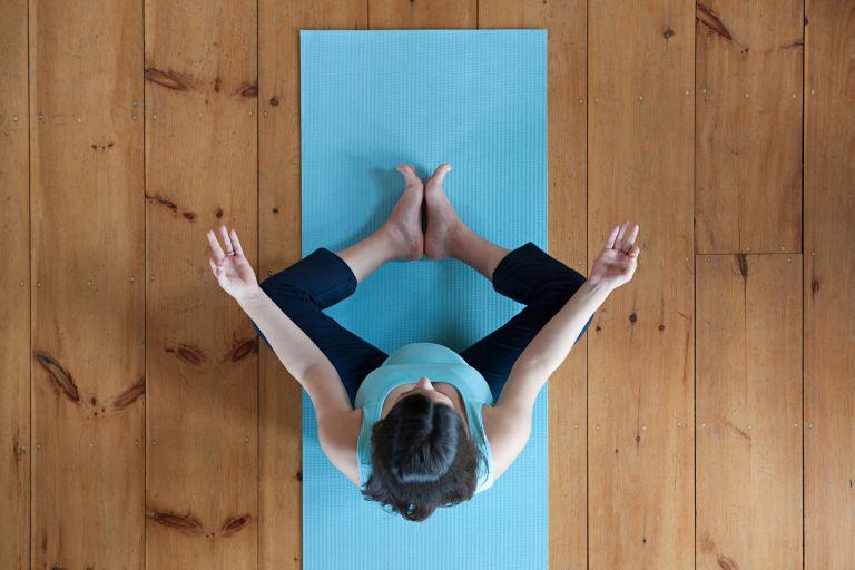 Overhead shot of a pregnant woman doing yoga on a blue yoga mat, best yoga mats