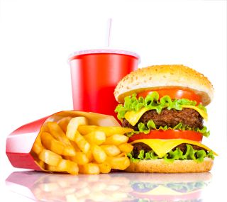A fast food burger piled high with toppings sits beside a large pile of french fries.