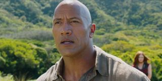 Dr. Xander Bravestone (Dwayne Johnson) stands in front of a lush jungle in 'Jumanji: Welcome to the Jungle'