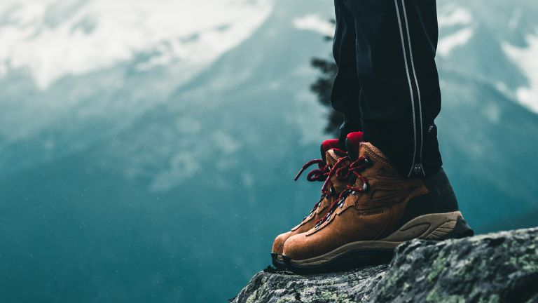best hiking boots: person standing on a rocky mountain