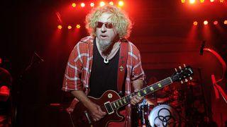 Rock singer Sammy Hagar onstage under red lights