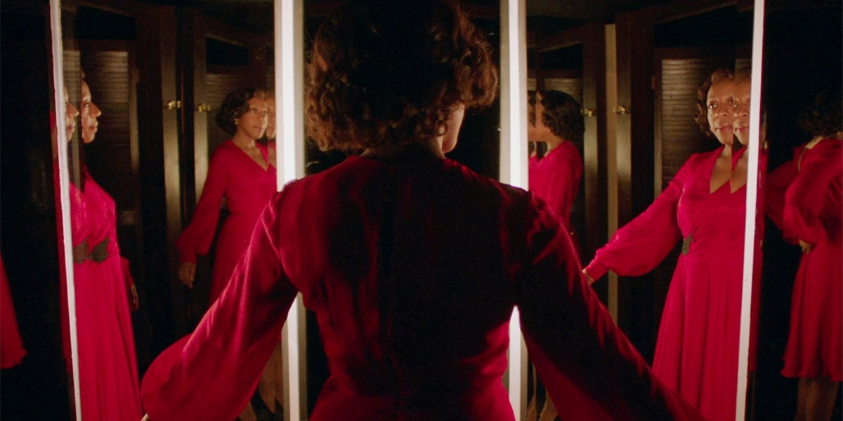 Marianne Jean-Baptiste standing in front of mirrors in In Fabric