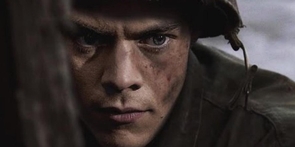Dunkirk Harry Styles in uniform, wearing a helmet, grimacing in place