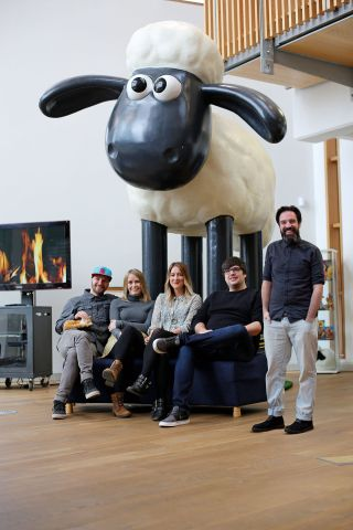 Aardman team posing in front of a Shaun the Sheep statue